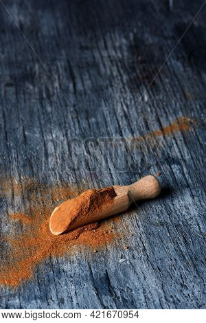 a wooden measuring scoop and full of camu-camu powder on a gray rustic wooden table
