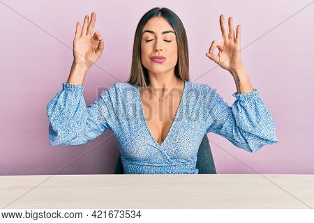 Young hispanic woman wearing casual clothes sitting on the table relax and smiling with eyes closed doing meditation gesture with fingers. yoga concept.