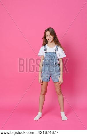 White Girl 10 Years Old In A White Top And Denim Shorts Smiling On A Pink Background, Emotions, Teen
