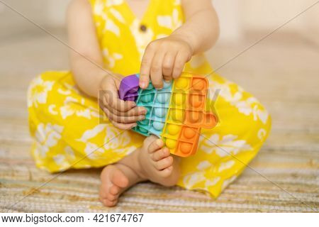A Little Girl Is Playing With A Modern Pop It Toy. A Fascinating Sensory Toy For The Development. Co