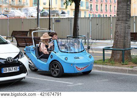 Nice, France - May 21, 2019: Nicecar Three-wheel Vehicle, Funny Small Blue Sharing Car, Young Couple