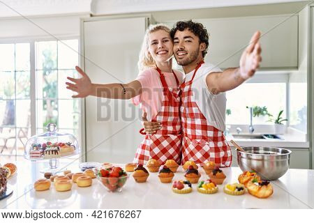 Couple of wife and husband cooking pastries at the kitchen looking at the camera smiling with open arms for hug. cheerful expression embracing happiness.