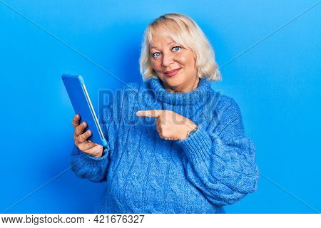 Middle age blonde woman using touchpad device smiling happy pointing with hand and finger