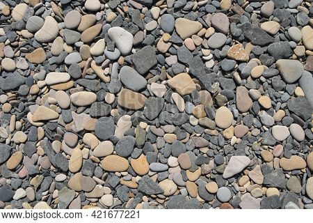 The Surface Texture Of Gray Sea Pebbles With Surf-smoothed Edges. Gray Pebbles Of The Sea Coast.