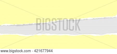 A Torn, Ripped Strip Of Yellow Paper With A Light Shadow On A Gray Background For Text. A Torn Piece