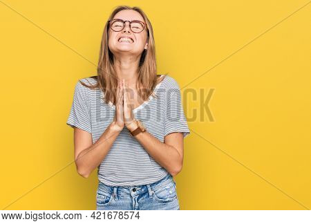 Beautiful young blonde woman wearing casual clothes and glasses begging and praying with hands together with hope expression on face very emotional and worried. begging.