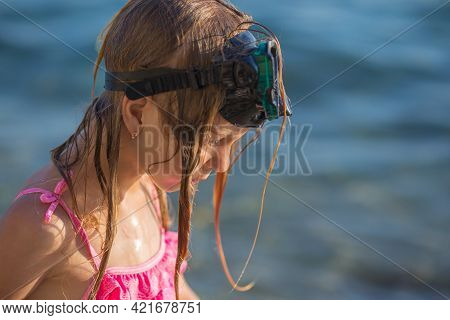 Little Girl With Swimming Glasses On Her Head, Got Out Of Sea Water, Soaking Wet.