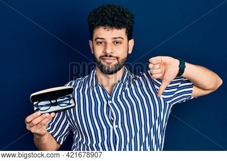 Young arab man with beard holding glasses in eyewear case with angry face, negative sign showing dislike with thumbs down, rejection concept