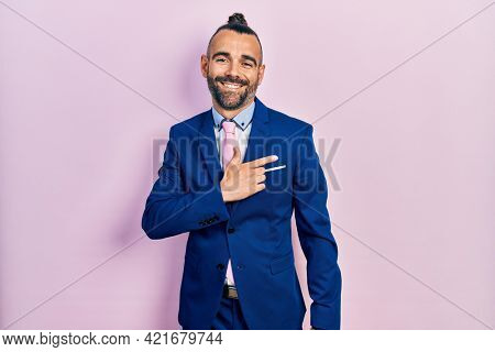 Young hispanic man wearing business suit and tie cheerful with a smile on face pointing with hand and finger up to the side with happy and natural expression