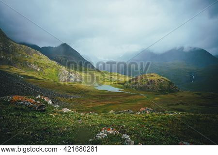 Dramatic Alpine Landscape With Beautiful Mountain Lake In Green Valley Among Great Rocks And High Mo