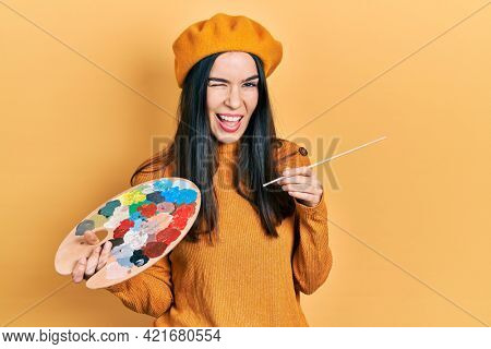 Young brunette woman holding paintbrush and palette wearing beret winking looking at the camera with sexy expression, cheerful and happy face.