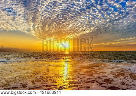 A Colorful Detailed Ocean Sunset Cloudscape As A Gentle Wave Rolls To The Seashore