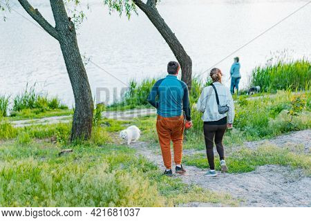 Couple Plays With White Dog And Going Down To The River In The Park. Leisure. Recreation. Forest. Na