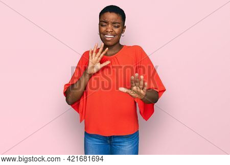Young african american woman wearing casual clothes disgusted expression, displeased and fearful doing disgust face because aversion reaction. with hands raised