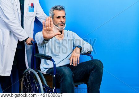 Handsome middle age man with grey hair on wheelchair wearing cervical collar doing stop sing with palm of the hand. warning expression with negative and serious gesture on the face.