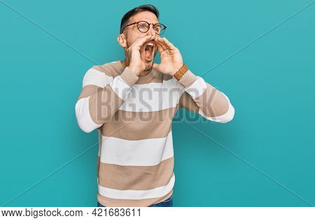 Handsome man with beard wearing casual clothes and glasses shouting angry out loud with hands over mouth