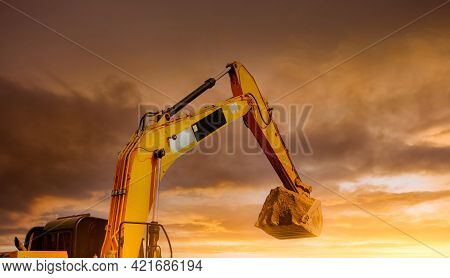 Backhoe Working By Digging Soil At Construction Site. Closeup Hydraulic Arm And Bucket Of Backhoe Wi