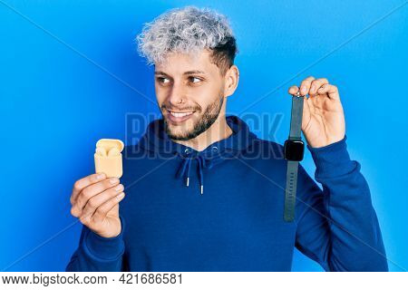 Young hispanic man with modern dyed hair holding wireless earphones and smart watch smiling looking to the side and staring away thinking.