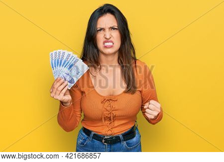 Beautiful hispanic woman holding 1000 south korean won banknotes annoyed and frustrated shouting with anger, yelling crazy with anger and hand raised