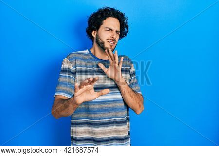 Handsome hispanic man wearing casual clothes over pink background disgusted expression, displeased and fearful doing disgust face because aversion reaction. with hands raised