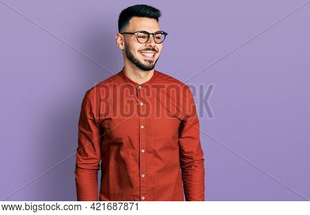 Young hispanic man with beard wearing business shirt and glasses looking away to side with smile on face, natural expression. laughing confident.