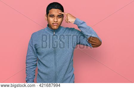 Young handsome hispanic man wearing casual sweatshirt pointing unhappy to pimple on forehead, ugly infection of blackhead. acne and skin problem