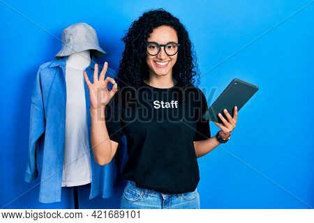 Young hispanic woman with curly hair wearing staff t shirt holding touchpad device doing ok sign with fingers, smiling friendly gesturing excellent symbol