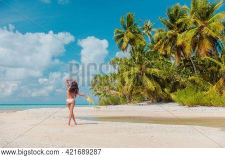 Beach vacation woman sunbathing relaxing on remote island in Rangiroa atoll, Tuamotu islands, French Polynesia. Tahiti travel dream destination bikini tourist girl relaxing walking on secluded beach.