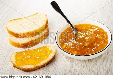 Slices Of Sweet Bun, Teaspoon In Bowl With Orange Jam, Sandwich With Jam On Wooden Table