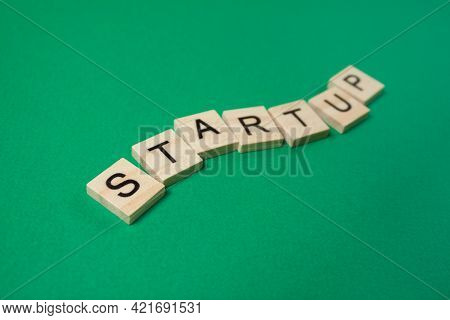 Word Startup Made Of Wooden Letters On A Green Background