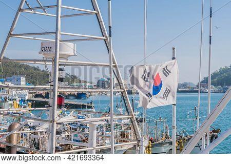 Sinjindo, South Korea; May 5, 2021: Korean Flag Waving From Mast Of Docked Fishing Trawler.