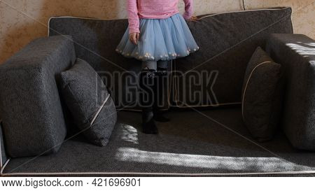 Kid Girl In Light Blue Tulle Tutu Skirt Stand On Couch With Pillows. Legs Of Girl Kid At Home