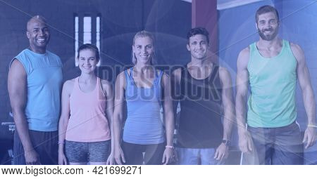 Composition of smiling men and women in fitness class with spot lights. sport, fitness and active lifestyle concept digitally generated image.