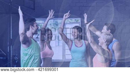 Composition of smiling men and women high fiving in fitness class with spot lights. sport, fitness and active lifestyle concept digitally generated image.