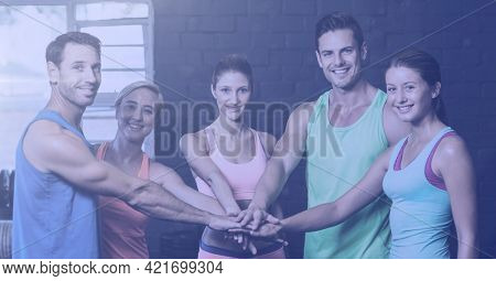 Composition of smiling men and women stacking hands in fitness class. sport, fitness and active lifestyle concept digitally generated image.