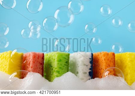 Household Cleaning Scrub Colored Sponges with soap foam and bubbles. Kitchen Dishwashing Sponge on blue background. Cleaning home concept. Space for text.