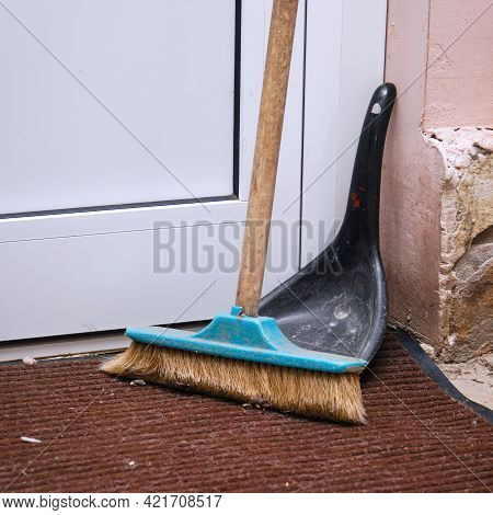 A Floor-sweeping Brush And A Scoop Stand In The Corner Near The Door