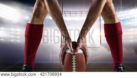 Composition of low section of rugby player with ball over sports stadium. sport event and competition concept digitally generated image.