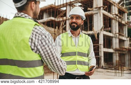 Positive Bearded Ethnic Male Engineer In Hardhat And Waistcoat Shaking Hand Of Colleague During Meet
