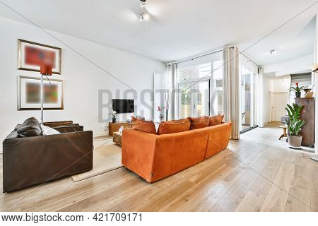 Spacious House Sitting Room With Comfortable Couches And Tv At Wall With Colorful Paintings And Glas