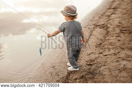 Full Body Side View Of Unrecognizable Cute Little Boy In Summer Clothes And Hat Standing Near Water,