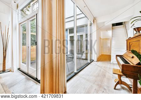 Glass Wall With Doorway Leading To Yard Of Modern House Furnished With Sofas And Piano