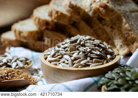 Closed Up Organic Sunflower Seeds In Wooden Bowl Over Blur Wholewheat Bread, Golden Flax And Pumpkin