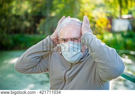 Sick, Sad Gray-haired Old Man Sits In A Medical Mask On The Street. The Man Has A Severe Headache. T