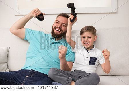 Cheerful Bearded Man And Little Son With Gamepads In Raised Hands Celebrating Victory While Playing