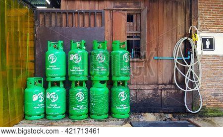 ฺbangkok, Thailand - May 5, 2021: Group Of Green Gas Tank With Wooden Background Putting Near Water