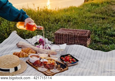 Womans Hand Pouring Rose Wine In A Glas