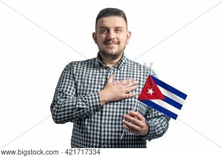 White Guy Holding A Flag Of Cuba And Holds His Hand On His Heart Isolated On A White Background With