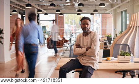 Portrait Of Businessman Sitting On Desk In Busy Multi-Cultural Office With Motion Blurred Colleagues