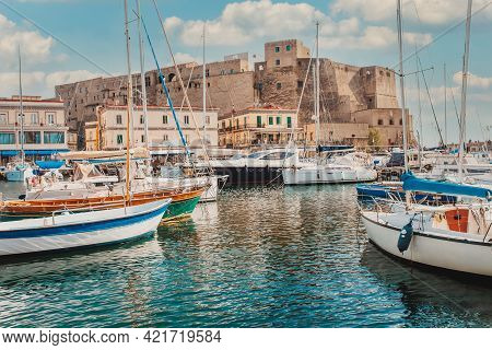 Castel Dell\\\'ovo Or Egg Castle a medieval fortress located in the Gulf of Naples. Famous historical mediterranean coast fortress port. Colorful buildings, yachts and boats, embankment and gulf of Naples